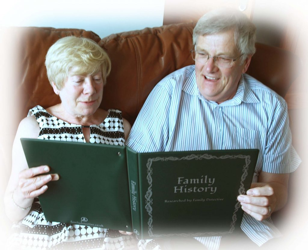 Couple on sofa laughing at something they're reading in their family history folder