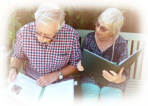 Couple sitting on garden bench looking at their family history folders